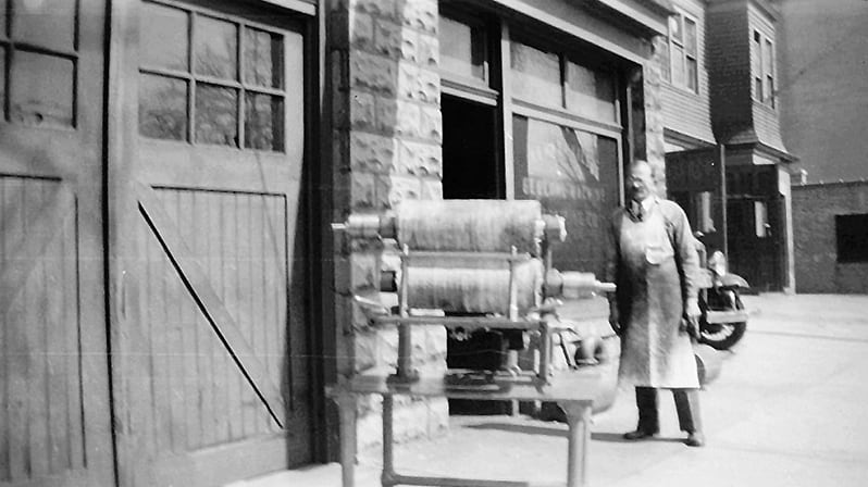 Photo of Joseph Wojtech in front of his general purpose machine shop in Newark, NJ